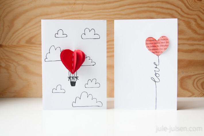 zwei Valentinstagskarten aus Papier: links = heissluftballon in Herzform in den Wolken, rechts = Luftballon in Herzform mit Schnur, die das Wort